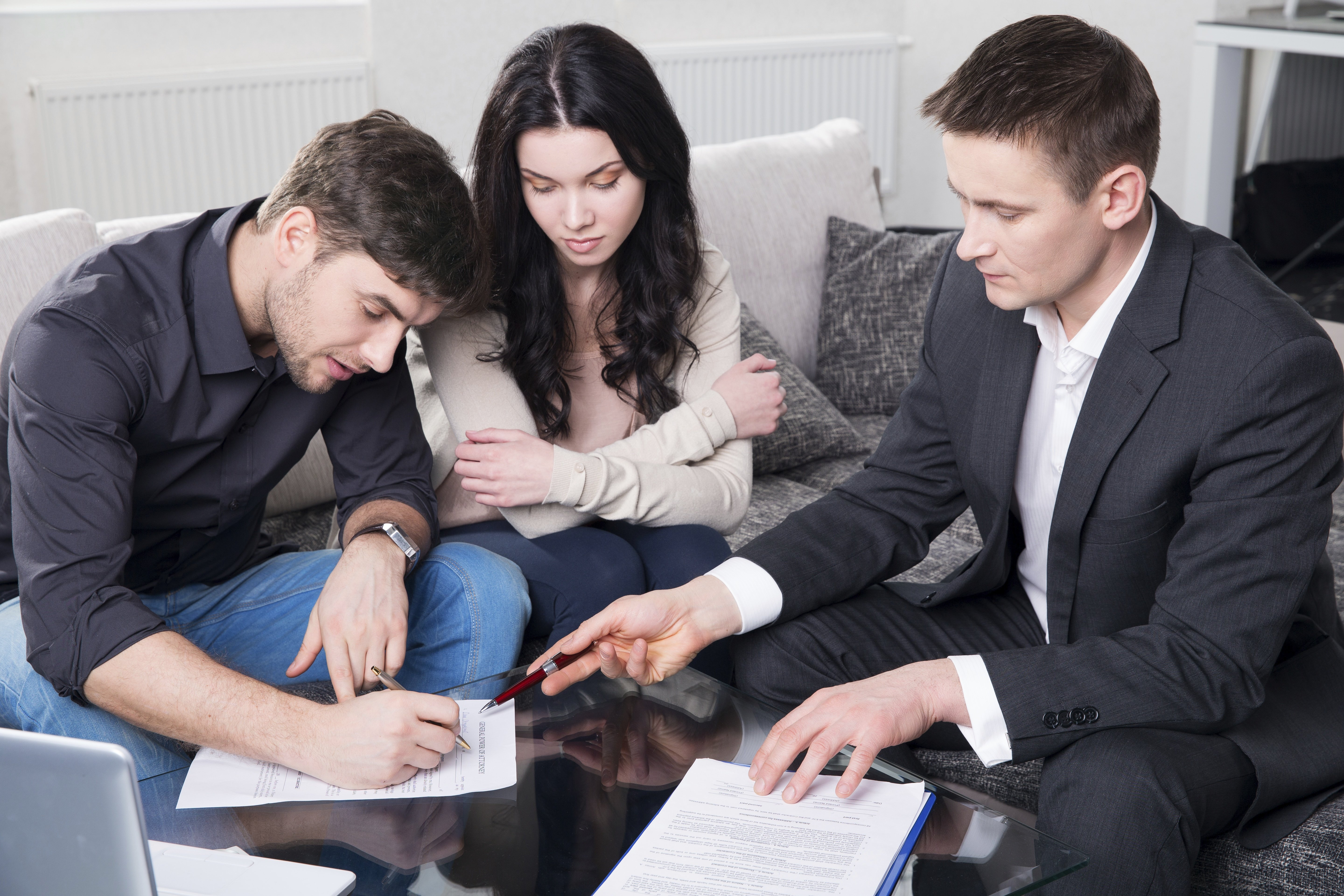 agent advising couple signing documents.jpg