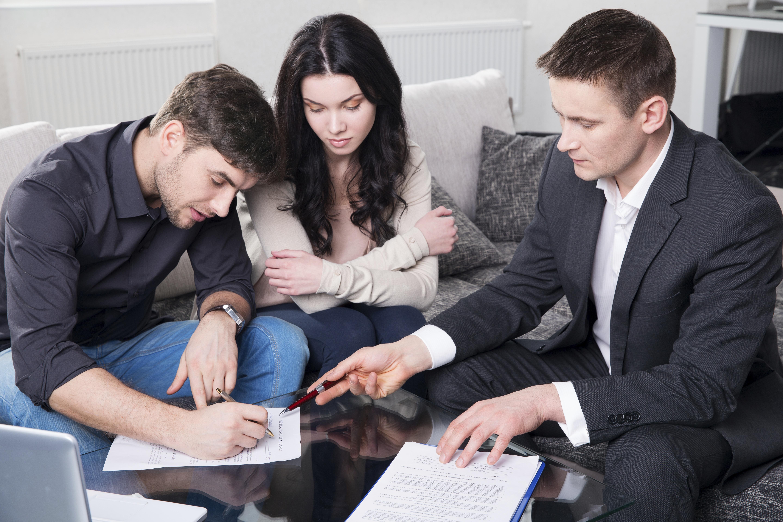 agent advising couple signing documents.jpg